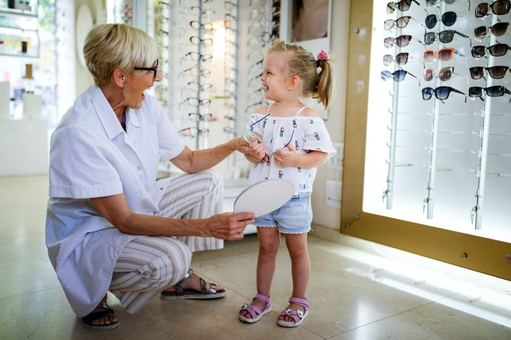 Child at eye sight test. Little kid selecting glasses at optician store