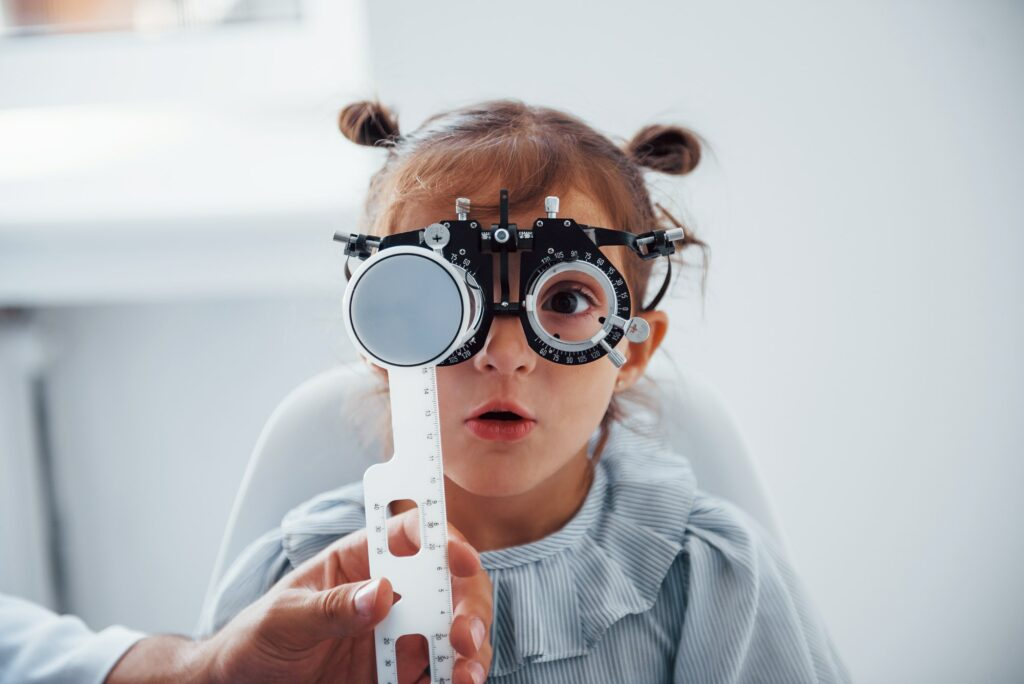 Little girl in eyewear in ophthalmology clinic have test of vision